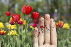 Conceptual family finger art. Father, son and daughter are giving flowers their mother. Stock Image. Happy Mother's Day, birthday and 8 March creative and funny Royalty Free Stock Photography