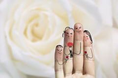 Conceptual family finger art. Father, son and daughter are giving flowers their mother. Stock Image. Happy Mother's Day, birthday and 8 March creative and funny Stock Images
