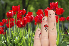 Conceptual family finger art. Father and son are giving flowers his mother. Stock Image. Royalty Free Stock Image