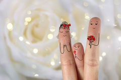 Conceptual family finger art. Father and son are giving flowers his mother. Stock Image. Happy Valentine's Day, wedding, 8 March, womans day, spring and birthday stock image