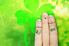 Conceptual finger art. Lovers are embracing and drinking beer. S. Saint Patrick's Day creative and funny lovelace love series. Painted fingers concept stock photo