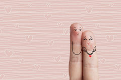 Conceptual finger art. Lovers is embracing and holding red heart. Stock  Royalty Free Stock Photo