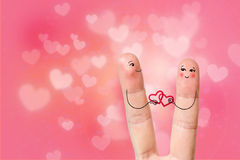 Conceptual finger art. Lovers are smiling and holding hearts. Stock Image Stock Photos