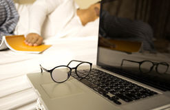 Conceptual focus on glasses businessman working on laptop  sleep Stock Photography