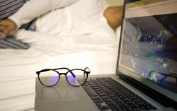 Conceptual focus on glasses businessman working on laptop sleeping on the bed stock photo