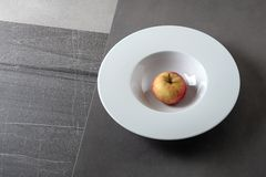 Conceptual food photography background: an apple in a white plate on a combined stone background.  stock photo
