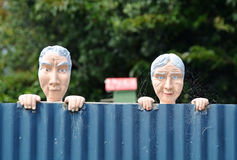 Conceptual funny nosy neighbours. Old man & woman looking over house fence Royalty Free Stock Photo