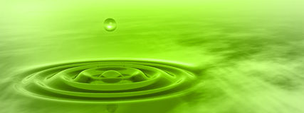 Conceptual green liquid drop falling in water banner. Conceptual green liquid drop falling in water with ripples and waves background banner Royalty Free Stock Photo
