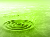 Conceptual green liquid drop falling in water Stock Image