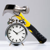 Conceptual Hammer Tool on a Round Alarm Clock Stock Photos