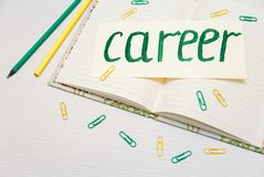 Conceptual hand drawn inscription: Career on the signboard.Green painting stroke sketch.Open notebook with pencils and clips.White. Table Stock Image