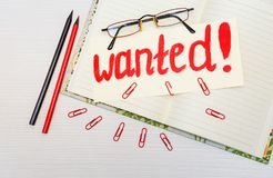 Conceptual hand drawn inscription:Wanted on the signboard.Red painting stroke sketch.Open notebook with pencils and clips,glasses. White table Stock Photography