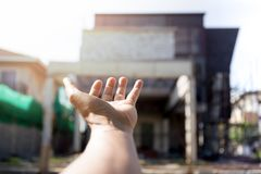Conceptual hand reaching for house on house construction site. In background Stock Image