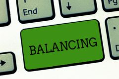 Conceptual hand writing showing Balancing. Business photo showcasing put something in a steady position so that it does. Not fall Keyboard Intention to create royalty free stock image