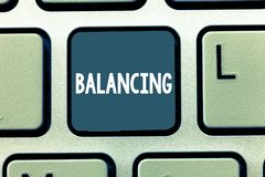 Conceptual hand writing showing Balancing. Business photo showcasing put something in a steady position so that it does. Not fall Keyboard Intention to create stock photography