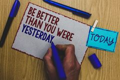 Conceptual hand writing showing Be Better Than You Were Yesterday. Business photo text try to improve yourself everyday Man holdin. G marker paper clothespin stock photography