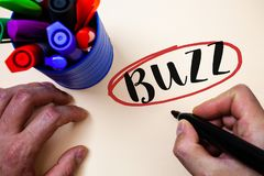 Conceptual hand writing showing Buzz. Business photo text Hum Murmur Drone Fizz Ring Sibilation Whir Alarm Beep Chime Man holding. Black marker markers table stock images