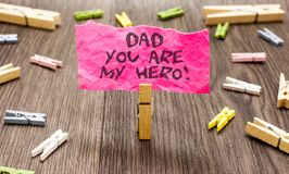 Conceptual hand writing showing Dad You Are My Hero. Business photo showcasing Admiration for your father love feelings compliment. Paperclip hold pink note royalty free stock images