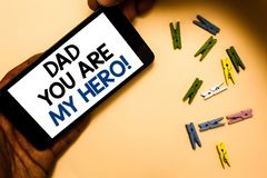 Conceptual hand writing showing Dad You Are My Hero. Business photo text Admiration for your father love feelings compliment Hand. Holding phone with letters stock photos