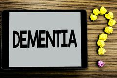 Conceptual hand writing showing Dementia. Business photo showcasing Long term memory loss sign and symptoms made me retire sooner. Written Tablet Screen wooden Stock Image