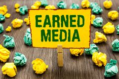Conceptual hand writing showing Earned Media. Business photo text Publicity gained through promotional efforts by multimedia Cloth. Espin holding yellow note royalty free stock photography
