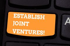 Conceptual hand writing showing Establish Joint Ventures. Business photo text Two or more companies invest in a certain business. Keyboard key Intention to stock image