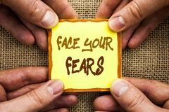 Conceptual hand writing showing Face Your Fears. Business photo showcasing Challenge Fear Fourage Confidence Brave Bravery written. Sticky Note Paper Holding royalty free stock image