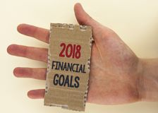 Conceptual hand writing showing 2018 Financial Goals. Business photo text New business strategy earn more profits less investment. Written Tear Cardboard Piece Stock Image