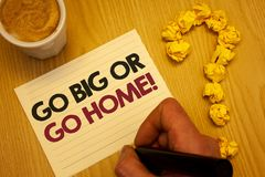 Conceptual hand writing showing Go Big Or Go Home Motivational Call. Business photo showcasing Mindset Ambitious Impulse Persisten. Ce Wooden desktop hand hold stock photo