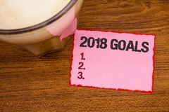 Conceptual hand writing showing 2018 Goals 1. 2. 3.. Business photo text Resolution Organize Beginnings Future Plans Wooden deskto. P red lined pink paper with royalty free stock photography