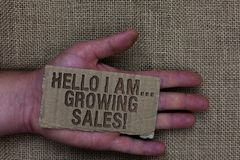 Conceptual hand writing showing Hello I Am... Growing Sales. Business photo text Making more money Selling larger quantities Cardb. Oard with marked some letters stock image