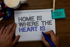 Conceptual hand writing showing Home Is When The Heart Is. Business photo showcasing Your house is where you feel comfortable and. Happy Hand hold pen paper stock photography