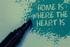Conceptual hand writing showing Home Is When The Heart Is. Business photo showcasing Your house is where you feel comfortable and. Happy Sprinkle blue color on royalty free stock photo