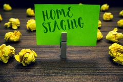 Conceptual hand writing showing Home Staging. Business photo text Act of preparing a private residence for sale in the market Clot. Hespin holding green paper stock images