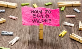 Conceptual hand writing showing How To Build Value question. Business photo showcasing Ways for developing growing building a busi. Ness Paperclip hold pink note royalty free stock photo
