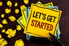 Conceptual hand writing showing Lets Get Started. Business photo showcasing beginning time motivational quote Inspiration encourag. E written Sticky Note Paper stock photos