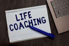 Conceptual hand writing showing Life Coaching. Business photo text Improve Lives by Challenges Encourages us in our Careers Open n. Otebook squared page black Stock Image