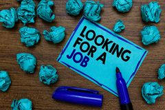 Conceptual hand writing showing Looking For A Job. Business photo showcasing Unemployed seeking work Recruitment Human Resources w. Ritten blue letters on page stock photo