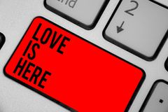 Conceptual hand writing showing Love Is Here. Business photo text Romantic feeling Lovely emotion Positive Expression Care Joy Key. Board red key create computer stock photos