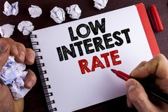 Conceptual hand writing showing Low Interest Rate. Business photo text Manage money wisely pay lesser rates save higher written by. Man Notepad wooden royalty free stock photo