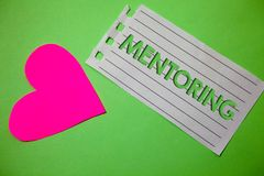 Conceptual hand writing showing Mentoring. Business photo showcasing To give advice or support to a younger less experienced perso. N Small paper drawing heart stock images