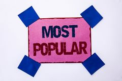 Conceptual hand writing showing Most Popular. Business photo text Top Rating Bestseller Favorite Product or Artist 1st in ranking. Written Pink Sticky Note stock photo