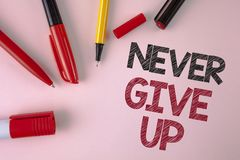 Conceptual hand writing showing Never Give Up. Business photo text Be persistent motivate yourself succeed never look back written. Plain Pink background Pens Stock Images