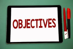 Conceptual hand writing showing Objectives. Business photo showcasing Goals planned to be achieved Desired targets Company mission. S Wide framed white tablet royalty free stock photography