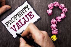 Conceptual hand writing showing Property Value. Business photo text Estimate of Worth Real Estate Residential Valuation written by. Man Sticky Note Holding Pen stock photo