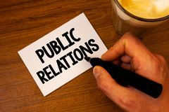Conceptual hand writing showing Public Relations. Business photo text Communication Media People Information Publicity Social Text. White paper hand black stock photography