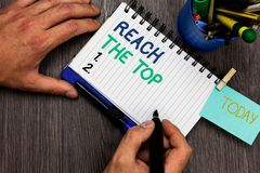 Conceptual hand writing showing Reach The Top. Business photo showcasing Get Ahead Succeed Prosper Thrive for the Win Victory Man. Holding marker notebook stock photos