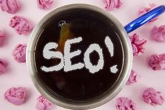 Conceptual hand writing showing Seo Motivational Call. Business photo showcasing Search Engine Optimization Marketing Keywording w. Ritten Tea in Cup within royalty free stock photography