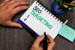 Conceptual hand writing showing Seo Targeting. Business photo showcasing Specific Keywords for Location Landing Page Top Domain Ma. N holding marker notebook royalty free stock photo