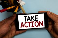 Conceptual hand writing showing Take Action. Business photo showcasing advices someone to do something or reaction right now Man h. Olding cell phone looking stock photography